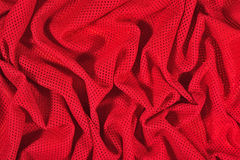 Red crumpled nonwoven fabric on a green Stock Image