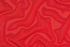 Red crumpled nonwoven fabric on a green Stock Images