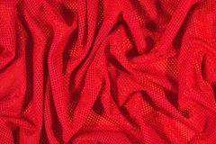 Red crumpled  nonwoven fabric on a yellow Royalty Free Stock Photography