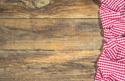 Red crumpled tablecloth on rustic brown wood. Royalty Free Stock Image