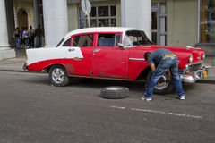 Red Cuban Car with flat tire from front. Havana, Cuba - Decemebr 25, 2010; Red classic car in Havana, Cuba, with with its tire being changed Royalty Free Stock Photos