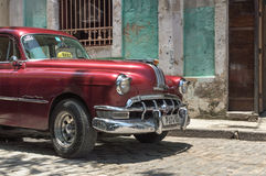 Red american taxi in Cuba. An old 50s american car parked in front of a colonial house with a treble clef painted on its wall Royalty Free Stock Photos