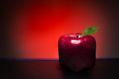 Red cube apple. Red, bitten, cube apple on a red background and black floor Royalty Free Stock Images