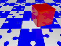 Red cube on puzzle pieces in blue and white colors Royalty Free Stock Image
