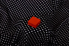 Red cube on te black material. Red cube on the black background with white dots Royalty Free Stock Photography