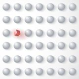 Red cube among white spheres, standing out in the Royalty Free Stock Photography