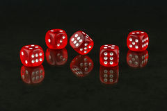 Red cubes for poker are reflected in the glass surface Royalty Free Stock Image