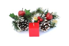 Red cubic candle with pine cone and holly. Christmas decoration Stock Image