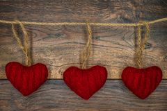 3 red cuddle hearts on twine with antique oak background, Valentine`s Day - front view stock photo