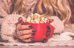 Red cup of appetizing golden popcorn in female hands. Female hands and cup of popcorn. Vintage tinting royalty free stock photography