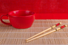 Red cup, bamboo sticks for sushi. Red cup, bamboo sticks on a red background Stock Images