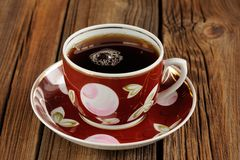 Red cup of black tea with bubbles on wooden background Royalty Free Stock Photo