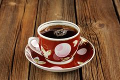 Red cup of black tea with bubbles on wooden background Stock Photography