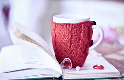 Red cup on the book with sweater. White cup with the red knitted thing on it staying on the open book Stock Images