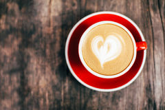 Red cup of cappucino with beautiful latte art Stock Photography