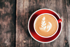 Red cup of cappucino with beautiful latte art Stock Photo