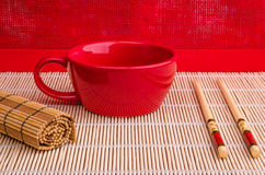 Red cup, chopsticks, a bamboo napkin. On a red background Royalty Free Stock Images