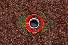 Red cup of coffee on coffee beans. Coffee mug on red plate full of beans surrounded by many roasted coffee seeds stock photography