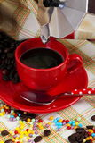 Red cup of coffee with coffee maker. On a background of colored cloth Royalty Free Stock Images