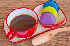 Red cup of coffee and colorful Biscuit on wooden table backgroun Royalty Free Stock Photos