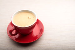 Red cup of coffee with frothy milk. On table Royalty Free Stock Photography
