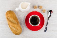 Red cup with coffee, jug of milk, bread, sugar cubes. Red cup with coffee on saucer, jug of milk, bread, sugar cubes and spoon on wooden table. Top view Stock Images