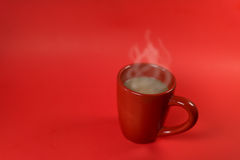 A red cup of coffee on the red background Stock Images
