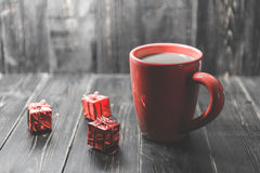A red cup of coffee with red Christmas ornament on the dark wooden background.. Royalty Free Stock Images