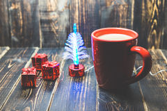 A red cup of coffee with red Christmas ornament on the dark wooden background.. Stock Image