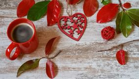 Red cup of coffee, red heart and autumn leaves on wooden background. Red cup of coffee, red heart and colorful autumn leaves on old white background Stock Photography