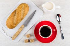 Red cup with coffee, sugar, bread, knife, jug of milk. Red cup with coffee on saucer, sugar cubes, bread and knife on cutting board, jug of milk, spoon on wooden Royalty Free Stock Photos