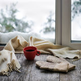 Red cup of coffee or tea, beige scarf and womans mittens. Red cup of coffee or tea, beige scarf and womans mittens are located on stylized wooden windowsill Stock Image