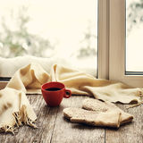 Red cup of coffee or tea, beige scarf and womans mittens. Red cup of coffee or tea, beige scarf and womans mittens are located on stylized wooden windowsill Stock Images