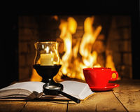 Red cup of coffee or tea, candle in lamp, magnifier glass and ol. D book on wooden table near fireplace. Winter and Christmas holiday concept Royalty Free Stock Images