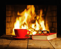 Red cup of coffee or tea, glasses and old book on wooden table n. Ear fireplace. Winter and Christmas holiday concept Stock Photo