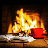 Red cup of coffee or tea, glasses and old book on wooden table near fireplace. royalty free stock image