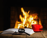 Red cup of coffee or tea, magnifier glass and old book on wooden. Table near  fireplace. Winter and Christmas holiday concept Royalty Free Stock Images