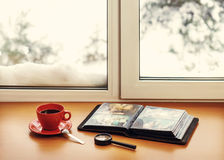 Red cup of coffee or tea with a metal spoon, photo album and lou. Pe located on a stylized wooden windowsill. Winter concept of comfort and relaxation. Photo Stock Photo