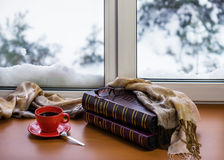 Red cup of coffee or tea with a metal spoon, photo albums and gl. Asses located on a stylized wooden windowsill. Winter concept of comfort and relaxation Stock Photo