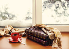 Red cup of coffee or tea with a metal spoon, photo albums and gl. Asses located on a stylized wooden windowsill. Winter concept of comfort and relaxation.  Photo Royalty Free Stock Photography