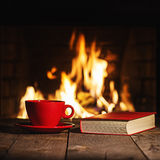 Red cup of coffee or tea and old book on wooden table near  fire. Place. Winter and Christmas holiday concept Royalty Free Stock Image