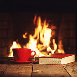 Red cup of coffee or tea and old book on wooden table near  fire. Place. Winter and Christmas holiday concept. Photo with retro filter effect Stock Images