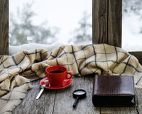Red cup of coffee or tea on stylized wooden windowsill. Red cup of coffee or tea with a metal spoon, a piece of sugar, photo album and loupe located on stylized Stock Images