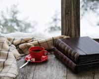 Red cup of coffee or tea on a stylized wooden windowsill. Red cup of coffee or tea with a metal spoon, a piece of sugar and two photo albums located on a Royalty Free Stock Photos