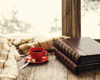 Red cup of coffee or tea on a stylized wooden windowsill. Red cup of coffee or tea with a metal spoon, a piece of sugar and two photo albums located on a Royalty Free Stock Photo
