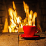 Red cup of coffee or tea on wooden table near  fireplace. Winter and Christmas holiday concept Royalty Free Stock Photos