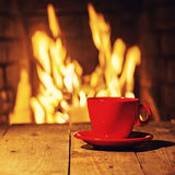 Red cup of coffee or tea on wooden table near  fireplace. Winter and Christmas holiday concept. Photo with retro filter effect Stock Image