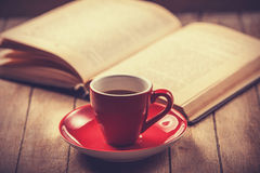 Red cup of the coffee and vintage book. Royalty Free Stock Photos