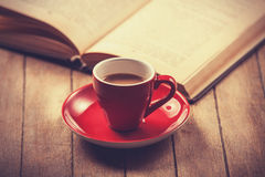 Red cup of the coffee and vintage book. Stock Photo