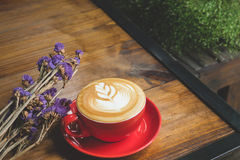 A red cup of coffee with vintage flower on wood table in coffee Royalty Free Stock Photo